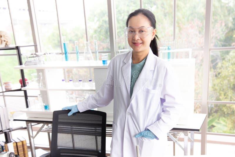 亚洲妇女科学家戴着眼镜在实验室屋子里站立 免版税库存照片