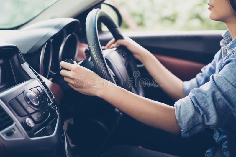 亚洲妇女` s递按钮转弯信号,按汽车, se 免版税库存图片