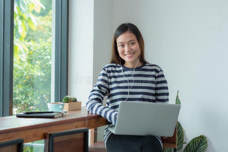 亚洲妇女influencer使用在便携式计算机上在窗口附近在c 免版税库存照片