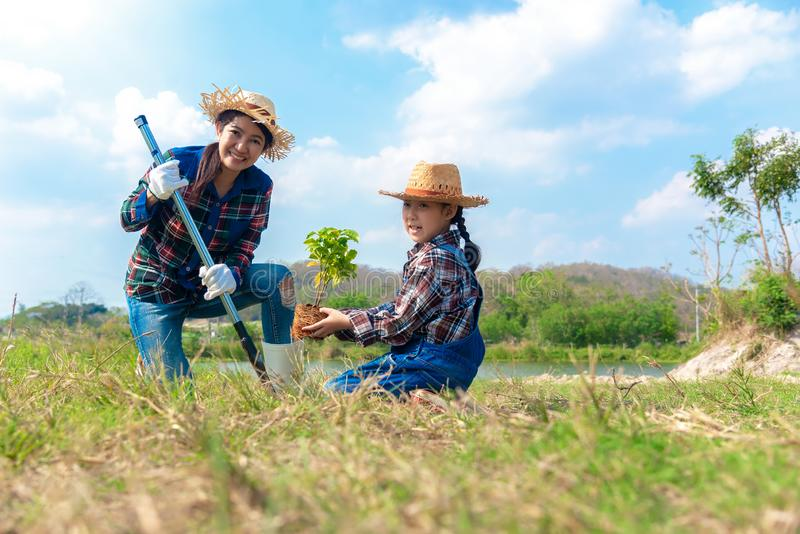 亚洲妈妈和儿童女孩植物树苗树在自然春天为减少全球性变暖成长特点和小心自然ea 库存图片