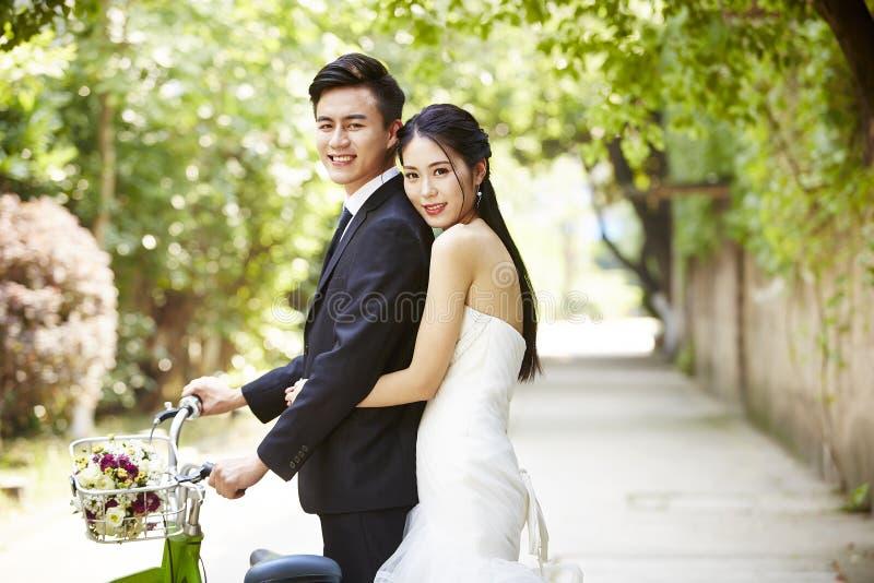 亚洲婚礼夫妇骑马自行车 免版税库存图片