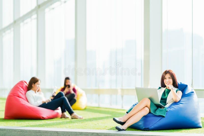 亚洲学生或企业队一起坐使用膝上型计算机,数字式片剂,智能手机在都市银行营业厅公园 库存照片
