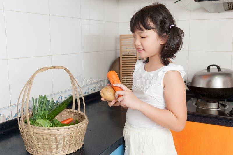 亚洲孩子在厨房里 免版税库存照片