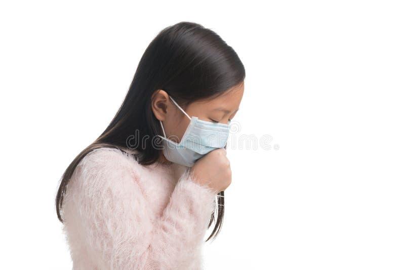 亚洲孩子女孩年龄与保护面具的7年反对流感viru 免版税库存图片