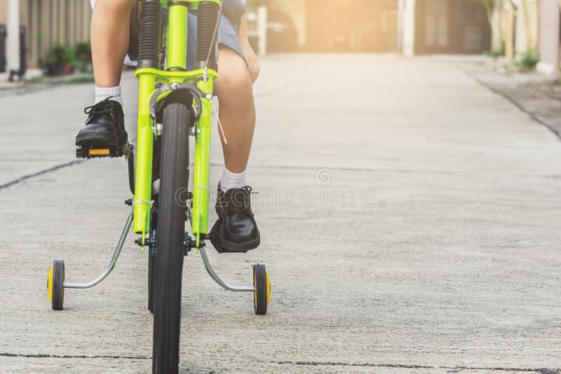 亚洲孩子学生锻炼自行车室外在生活方式乐趣愉快的乘驾骑自行车的训练享用的村庄前面学会 库存照片