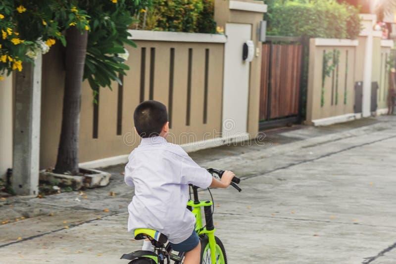亚洲孩子学生锻炼自行车室外在生活方式乐趣愉快的乘驾骑自行车的训练享用的村庄前面学会 免版税库存照片