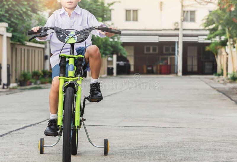 亚洲孩子学生锻炼自行车室外在生活方式乐趣愉快的乘驾骑自行车的训练享用的村庄前面学会 免版税库存图片