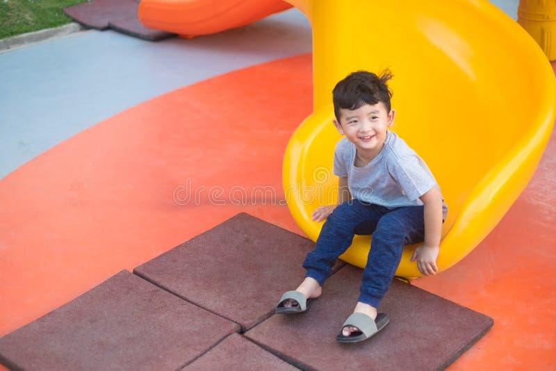 亚洲孩子演奏幻灯片的在操场在阳光下在夏天,愉快的孩子在幼儿园或学龄前校园 免版税库存图片