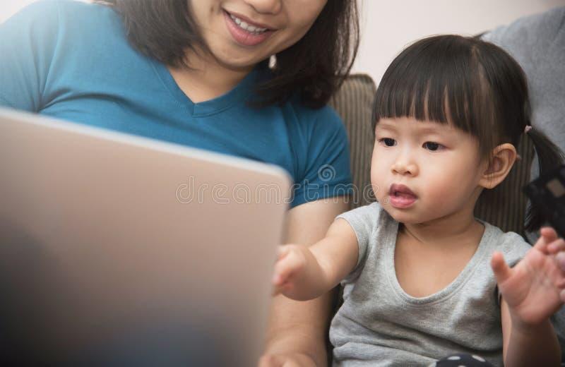 亚洲家庭开会和一起使用膝上型计算机的幸福 免版税库存图片