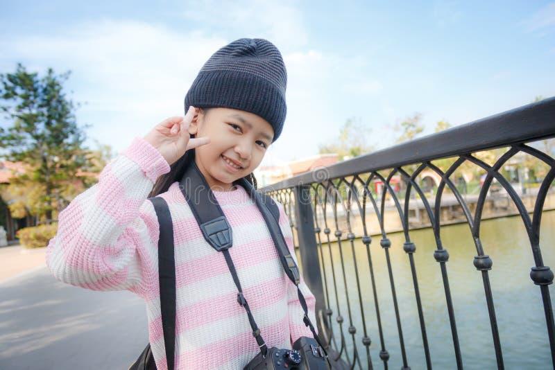 亚洲小女孩微笑和显示充满幸福的胜利标志 免版税库存图片