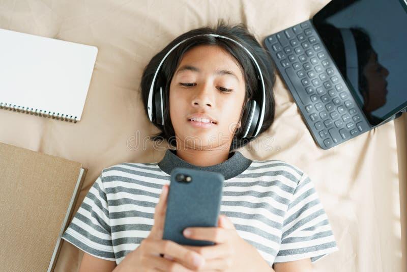 亚洲小女孩的头像是早晨在家里的床上戴着耳机,在智能手机上听音乐 库存图片