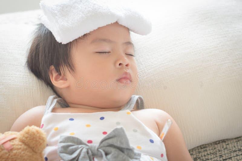 亚洲小女孩睡眠和病残沙发的有更加凉快的胶凝体的在她 免版税图库摄影