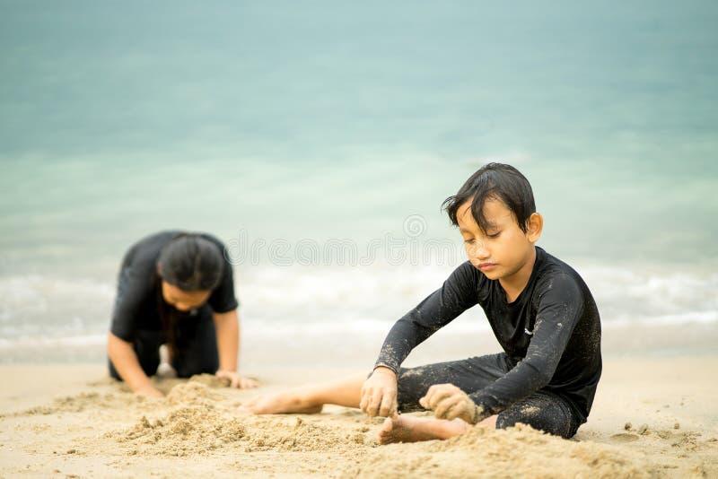 亚洲小孩在沙滩上玩耍 免版税库存照片