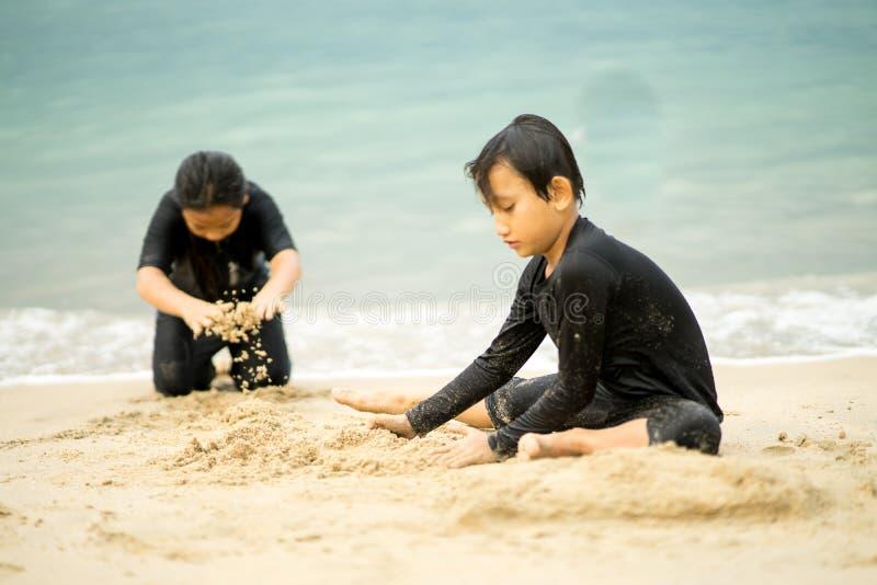 亚洲小孩在沙滩上玩耍 免版税图库摄影