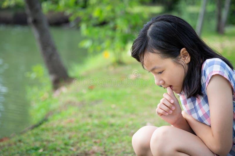 亚洲小孩女孩感觉在室外公园,有紧张的表示的女孩病人注重了,女性担心的叮咬手指甲, 免版税库存照片