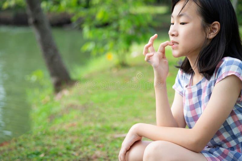 亚洲小孩女孩感觉在室外公园,有紧张的表示的女孩病人注重了,女性担心的叮咬手指甲, 免版税图库摄影