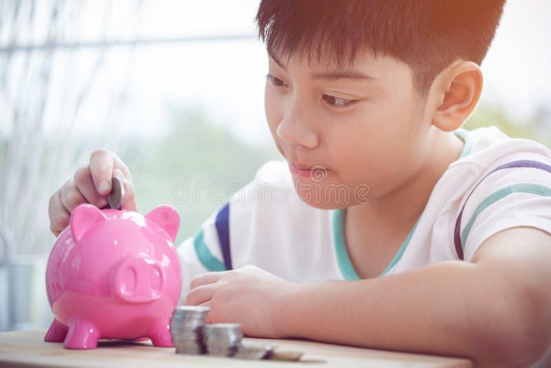 亚洲小男孩挽救金钱在桃红色存钱罐中 库存照片