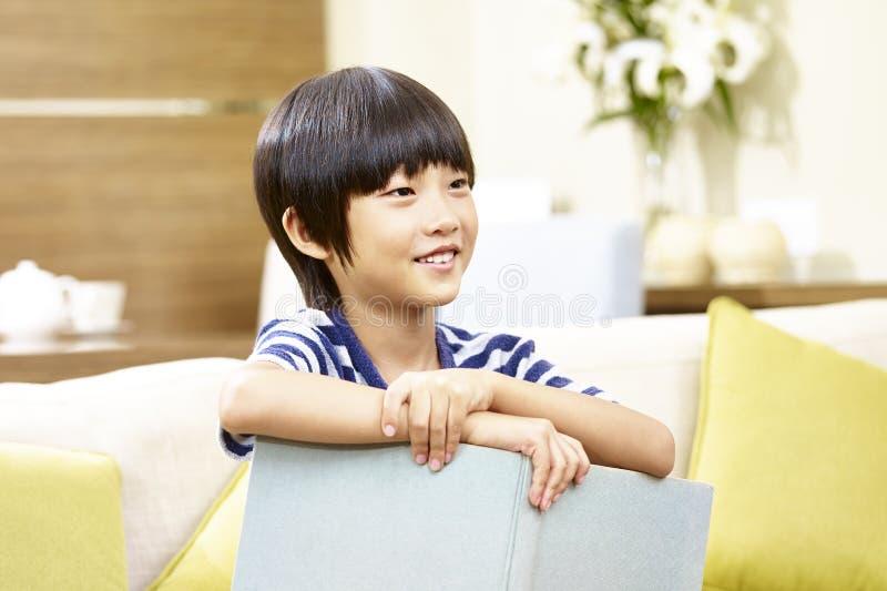 亚洲小男孩阅读书在家 免版税库存图片