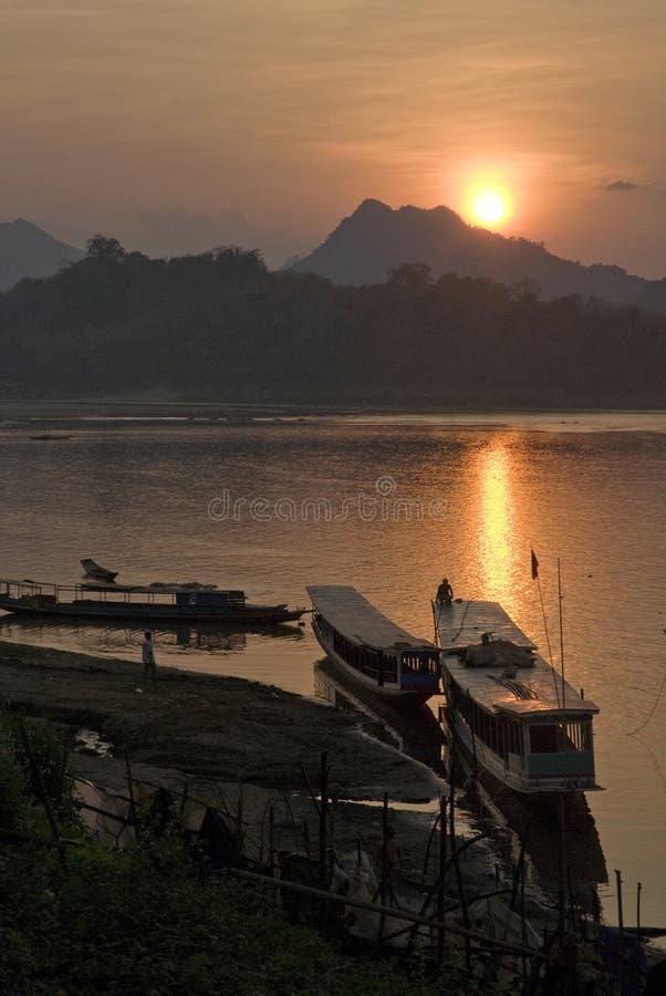 亚洲小船老挝luang prabang河日落 库存图片