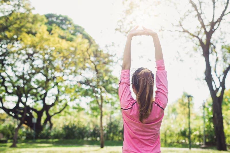 亚洲少妇准备舒展在早晨锻炼和瑜伽前的身体在公园在温暖的轻的早晨下 免版税库存照片