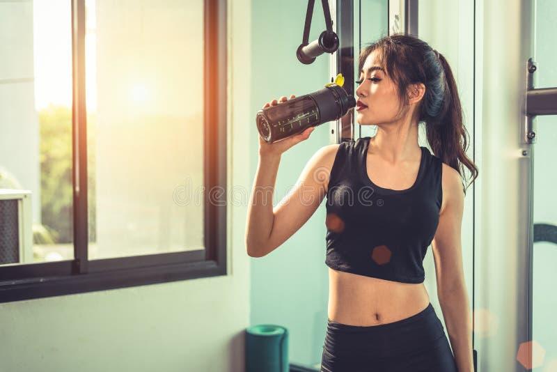 亚洲少妇饮用的蛋白质震动或水在锻炼以后 免版税图库摄影