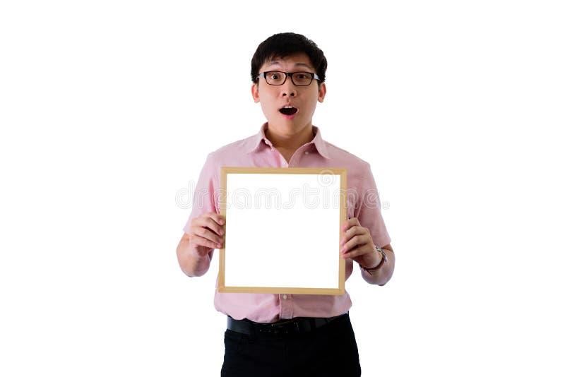 亚洲年轻商人在隔绝有身分和拿着与惊奇的空白的白色屏板在wihte背景 图库摄影