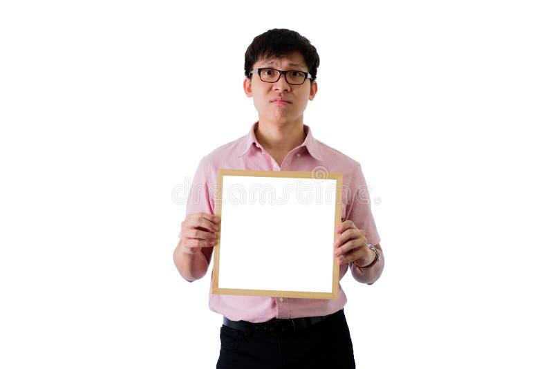 亚洲年轻商人在wihte背景有身分和拿着空白的白色屏板以不快乐在隔绝 免版税库存照片