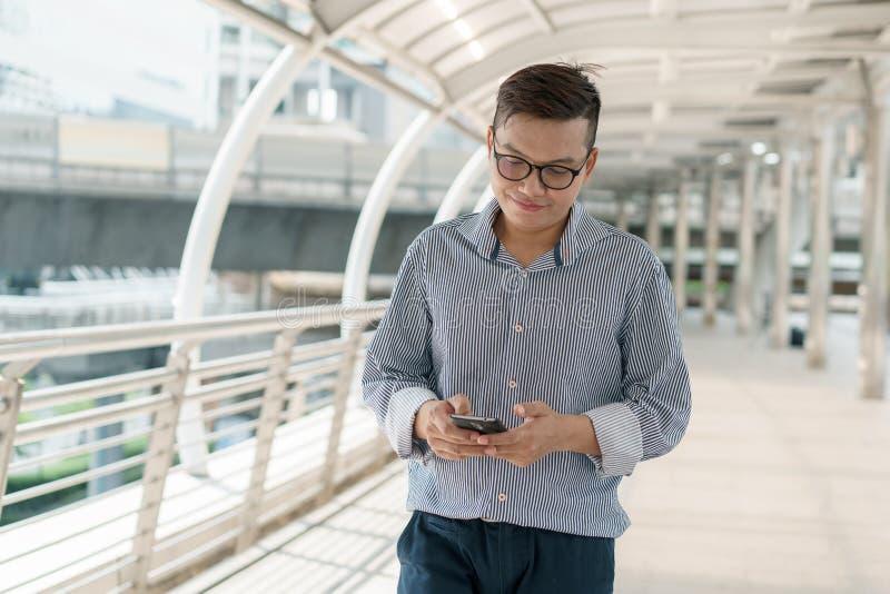 亚洲年轻商人身分画象在外部办公室 微笑和看智能手机的年轻商人穿戴衣服 图库摄影