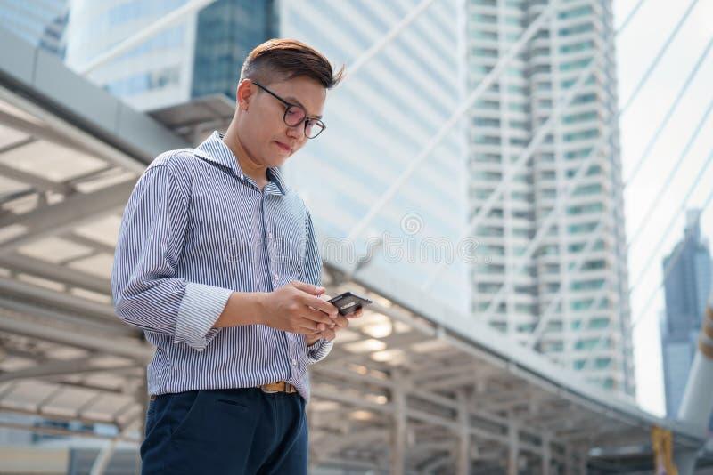 亚洲年轻商人身分画象在外部办公室 微笑和看智能手机的年轻商人穿戴衣服 库存照片