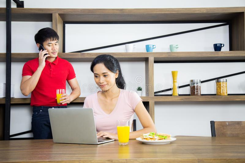 亚洲年轻夫妇,妇女看在膝上型计算机的事务和后边有谈一个的人手机 库存图片