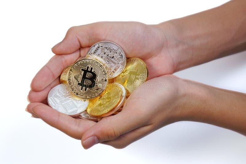 亚洲年轻手阻止许多金黄bitcoin和银色bitcoin在两手上 关闭bitcoin在白色隔绝的开放手上 库存图片