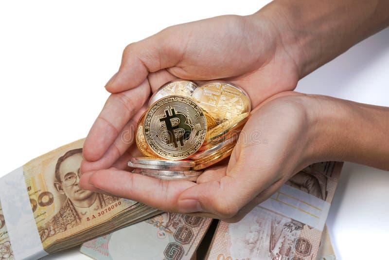 亚洲年轻手阻止许多金黄bitcoin和银色bitcoin在两移交泰国钞票在背景中 库存图片