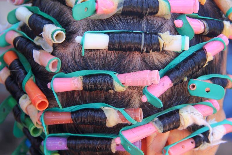 亚洲年长妇女头和五颜六色的塑料路辗用头发电烫解答,卷曲的处理背景 库存图片