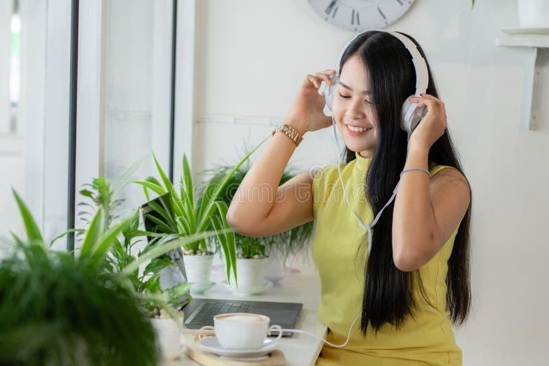 亚洲微笑女学生在咖啡馆与skype老师在线学习无线耳机,女性学习语言听 库存图片