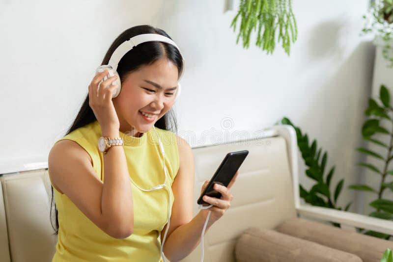 亚洲微笑女学生在咖啡馆与skype老师在线学习无线耳机,女性学习语言听 库存照片