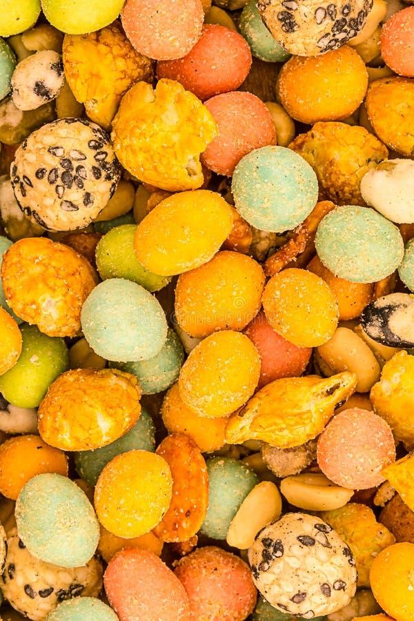 亚洲快餐给锋利的快餐多彩多姿的黄色桃红色糖衣杏仁坚果快餐背景可食的设计上釉 免版税库存图片