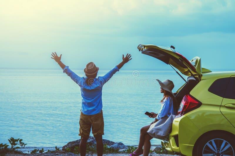亚洲恋人夫妇妇女和人旅行自然 r 坐在海滩的汽车 在夏天 免版税库存照片