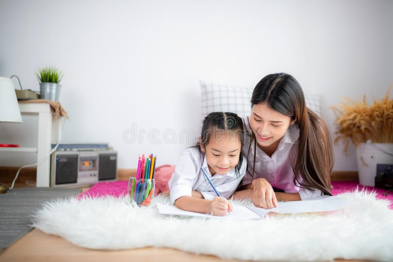 亚洲愉快的爱恋的家庭 俏丽的年轻母亲写书 免版税图库摄影