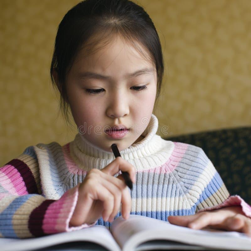 亚洲执行的女孩家庭作业 免版税库存照片
