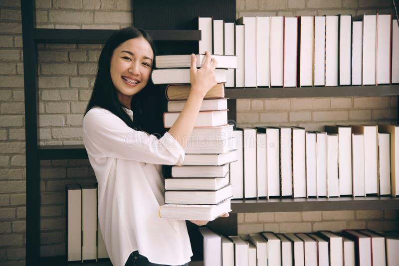 亚洲拿着书的女学生在图书馆学校 免版税库存图片