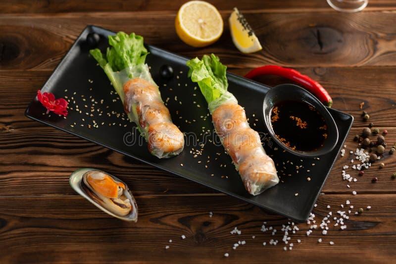 亚洲春卷用在黑长方形板材的虾 库存图片