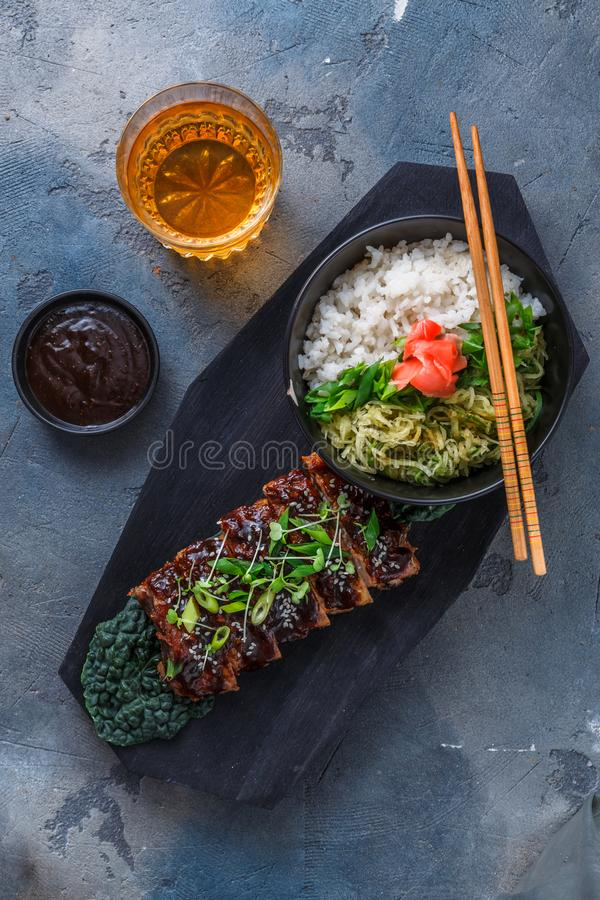 亚洲样式bbq猪排用调味汁和米在木板,顶视图 免版税库存图片