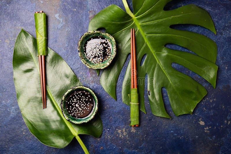 亚洲概念食物 筷子和soysauce酱油用在蓝色背景的白色芝麻与热带叶子 顶层 图库摄影