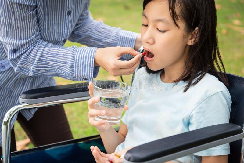 亚洲母亲或照料者医学药片或胶囊在手中或手指,给药片儿童女孩,病态女儿采取,吃 库存照片