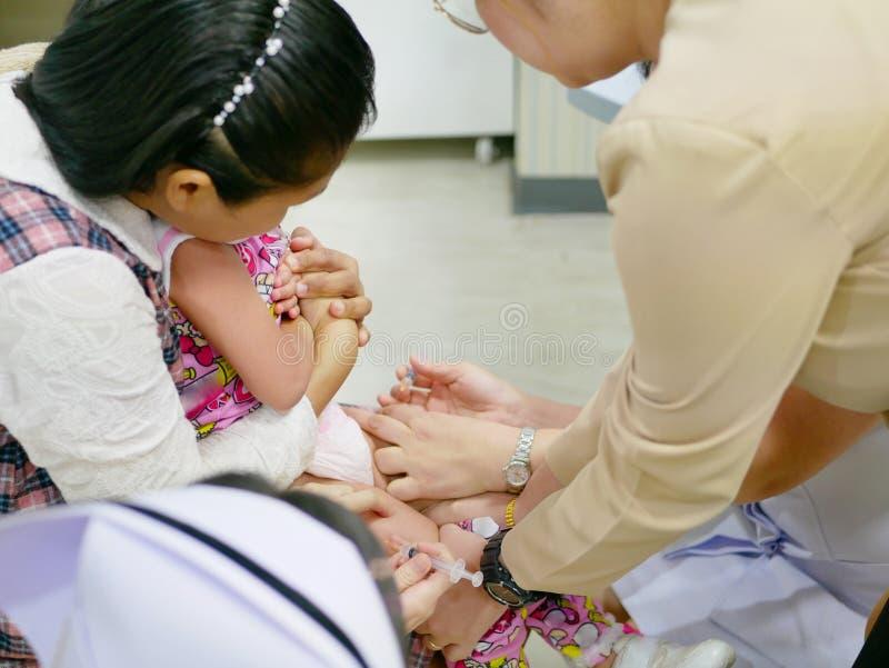 亚洲母亲` s递拥抱她的女儿,当接受双重接种时 免版税库存图片