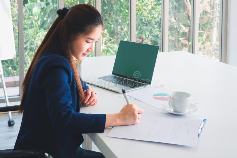 亚洲水军蓝色衣服工作的长发美丽的女商人,写文件在桌在办公室 树窗口外 图库摄影