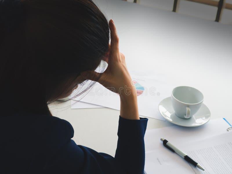 亚洲水军蓝色衣服张力的长发美丽的女商人与工作util头疼在她的办公室 有咖啡杯,笔,rep 免版税图库摄影