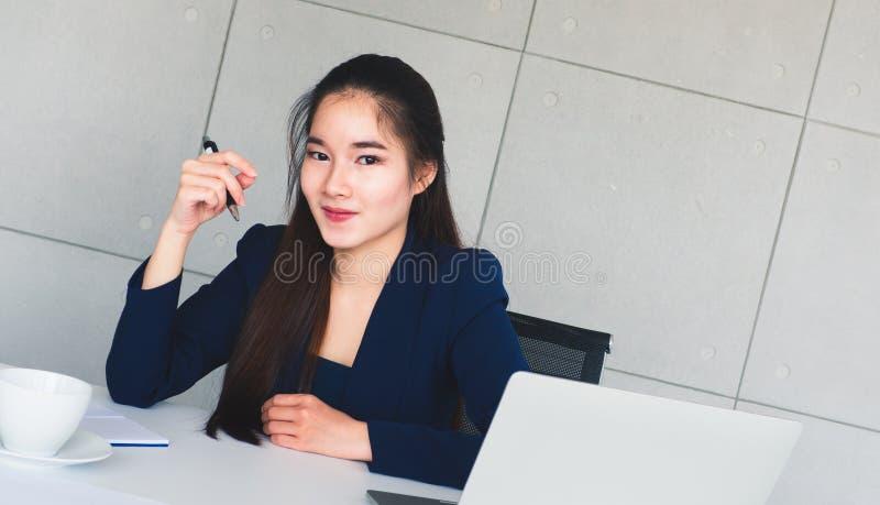 亚洲水军蓝色衣服微笑的长发美丽的女商人很愉快在她的桌上在办公室 有咖啡杯,膝上型计算机,documen 免版税库存照片