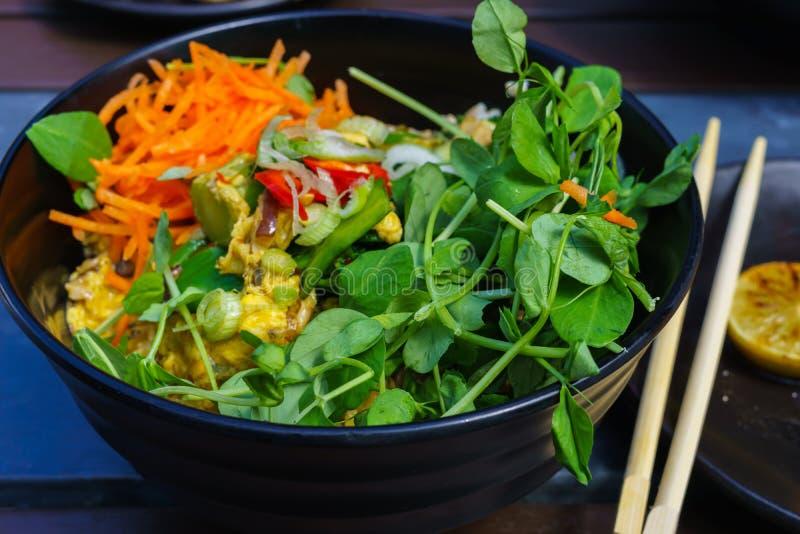 亚洲炒米用鸡蛋和菜和seefoodsand发芽了豌豆,在blak盘服务用在木背景的幻灯片黄瓜 库存照片