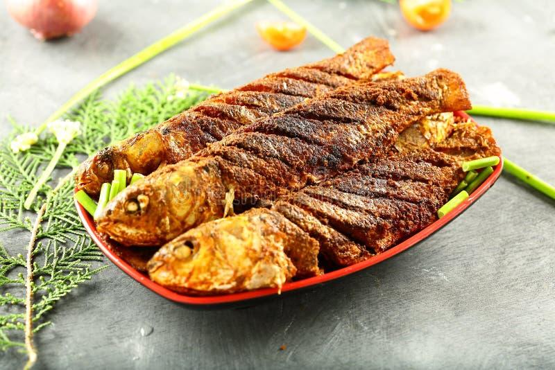 亚洲烹调,烤鱼用异乎寻常的香料 库存照片